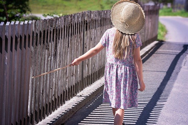 A girl standing in front of a fence